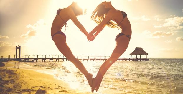 Dvě dívky v bikinách na pláži skočí a vytvoří srdce na dovolené u moře s cestovkou